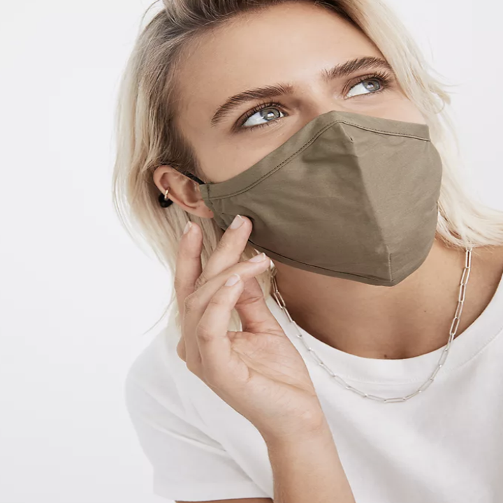 Model in a faded green face mask