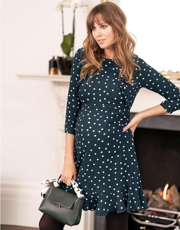 a pregnant model wearing a long-sleeve mini dress in blue with white polka dots