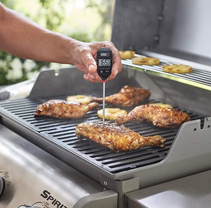 A person probing a chicken leg on the BBQ to check its temperature