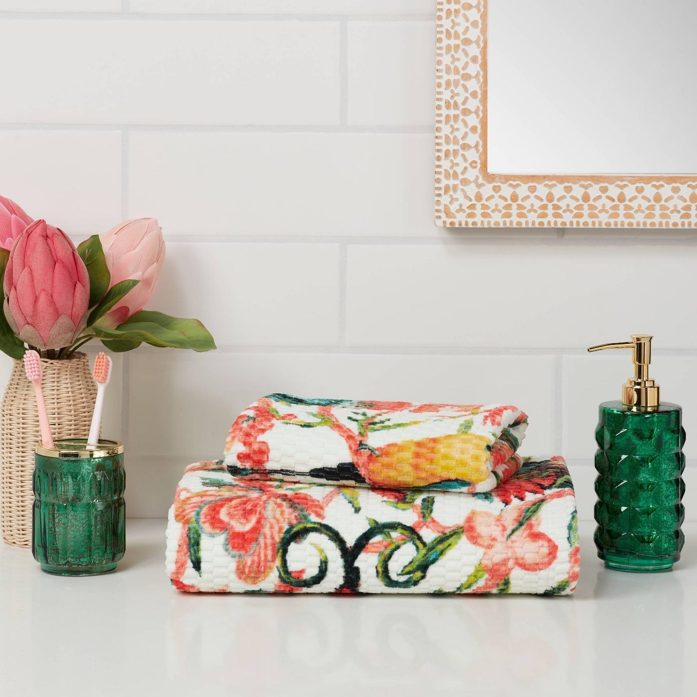 The colorful bird floral towels beside green accessories and a white backsplash