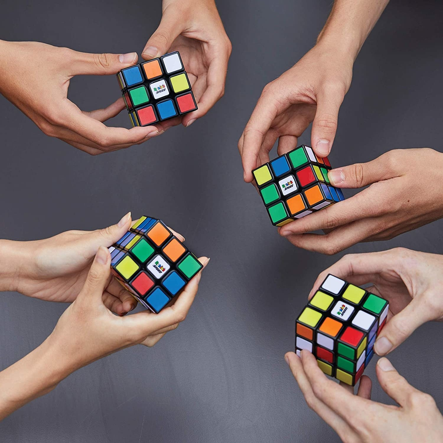 Four people playing with Rubik's cubes