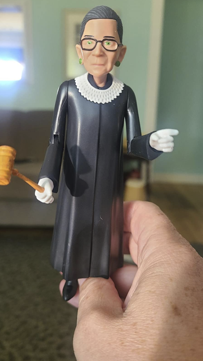 reviewer's hand holding the RBG action figure which is wearing her signature judge robe, collar, and holding a gavel