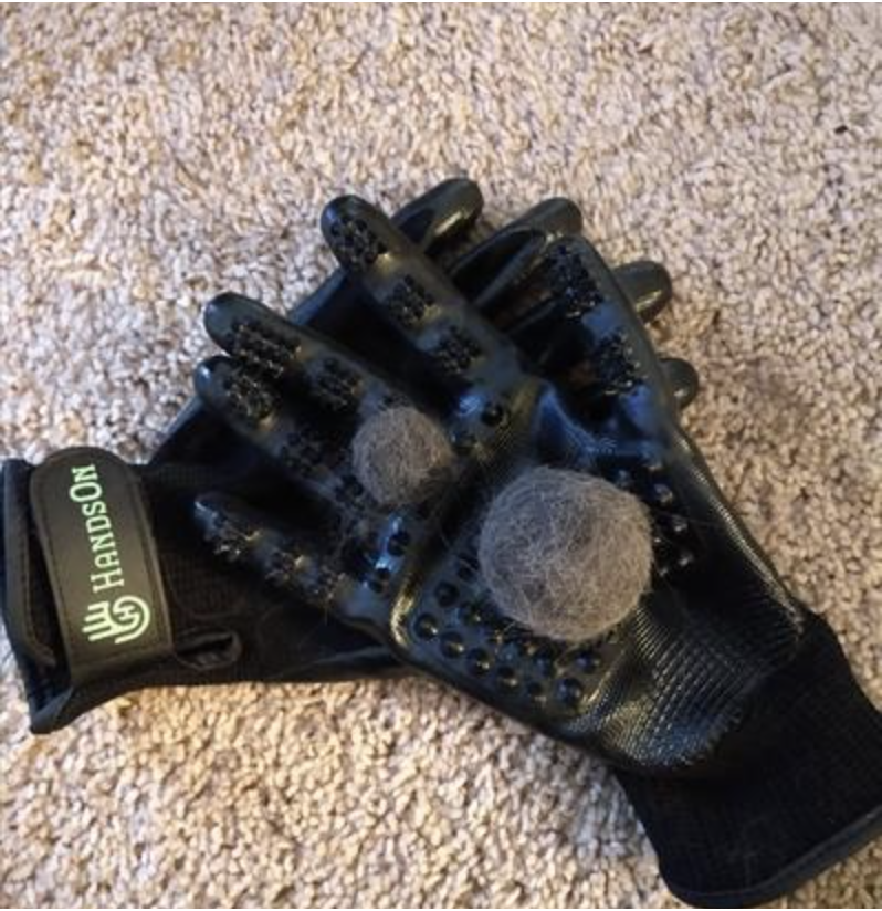 a pair of gloves in black with the two balls of pet hair on them
