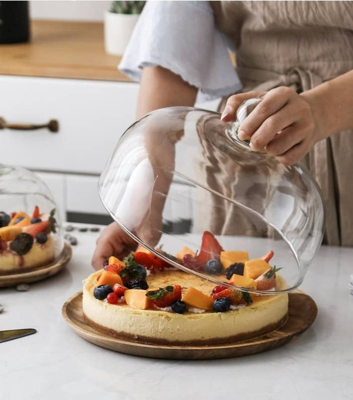 A hand lifting the glass lid off of a large walnut cake stand