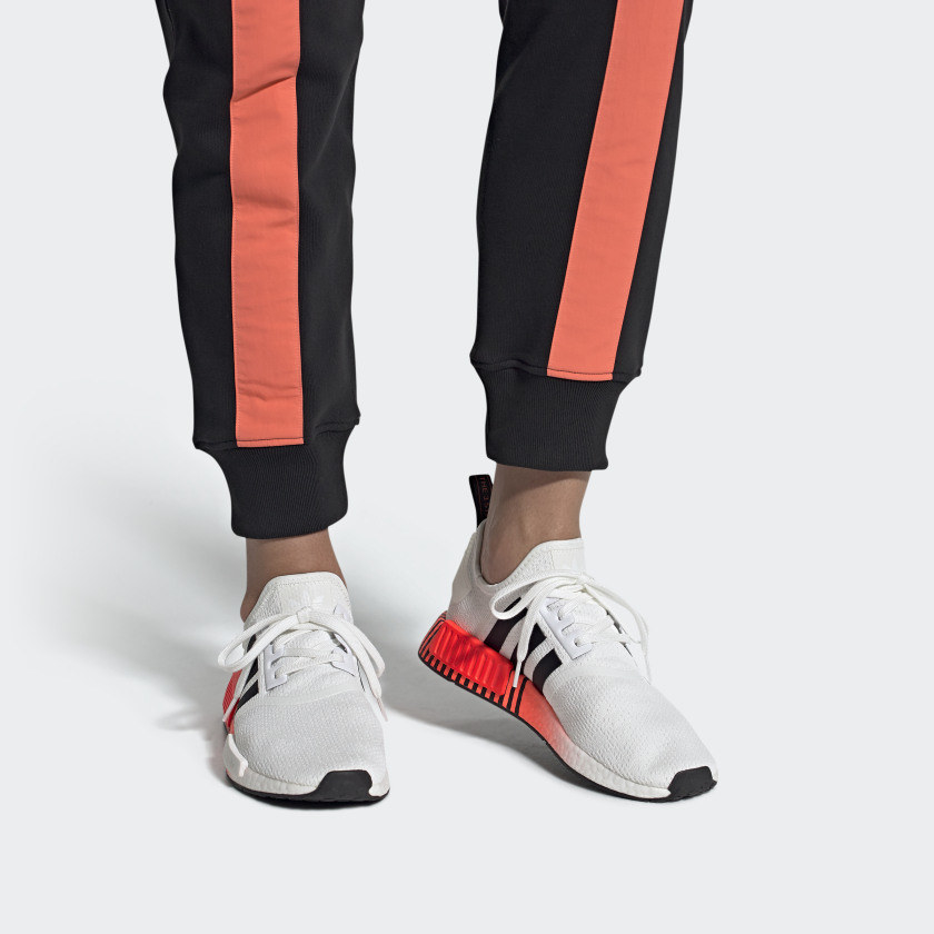 model wearing lace-up white sneakers with black adidas stripes and orange accents on the sides of the soles