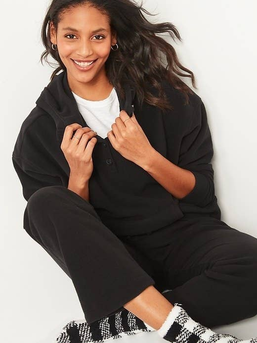 Model wearing black hoodie and black joggers