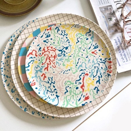 A stack of four bamboo plates with colorful '80s designs