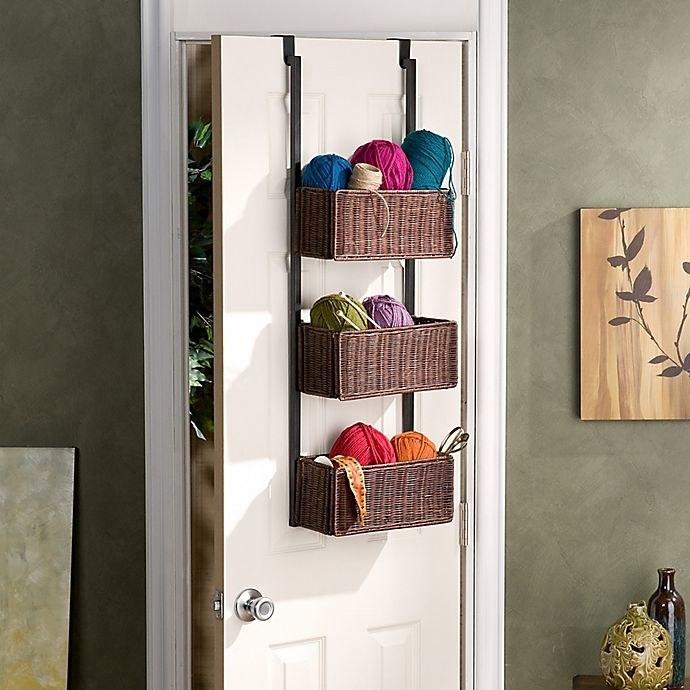 the Southern Enterprises Over-The-Door 3-Tier Basket Storage handing on the back of a door