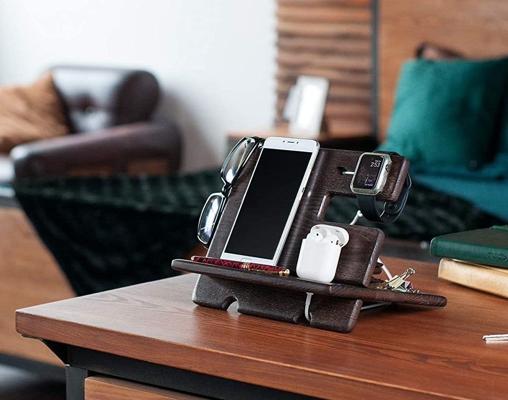A docking station on a table holding a pair of glasses, a phone, earphones, and keys