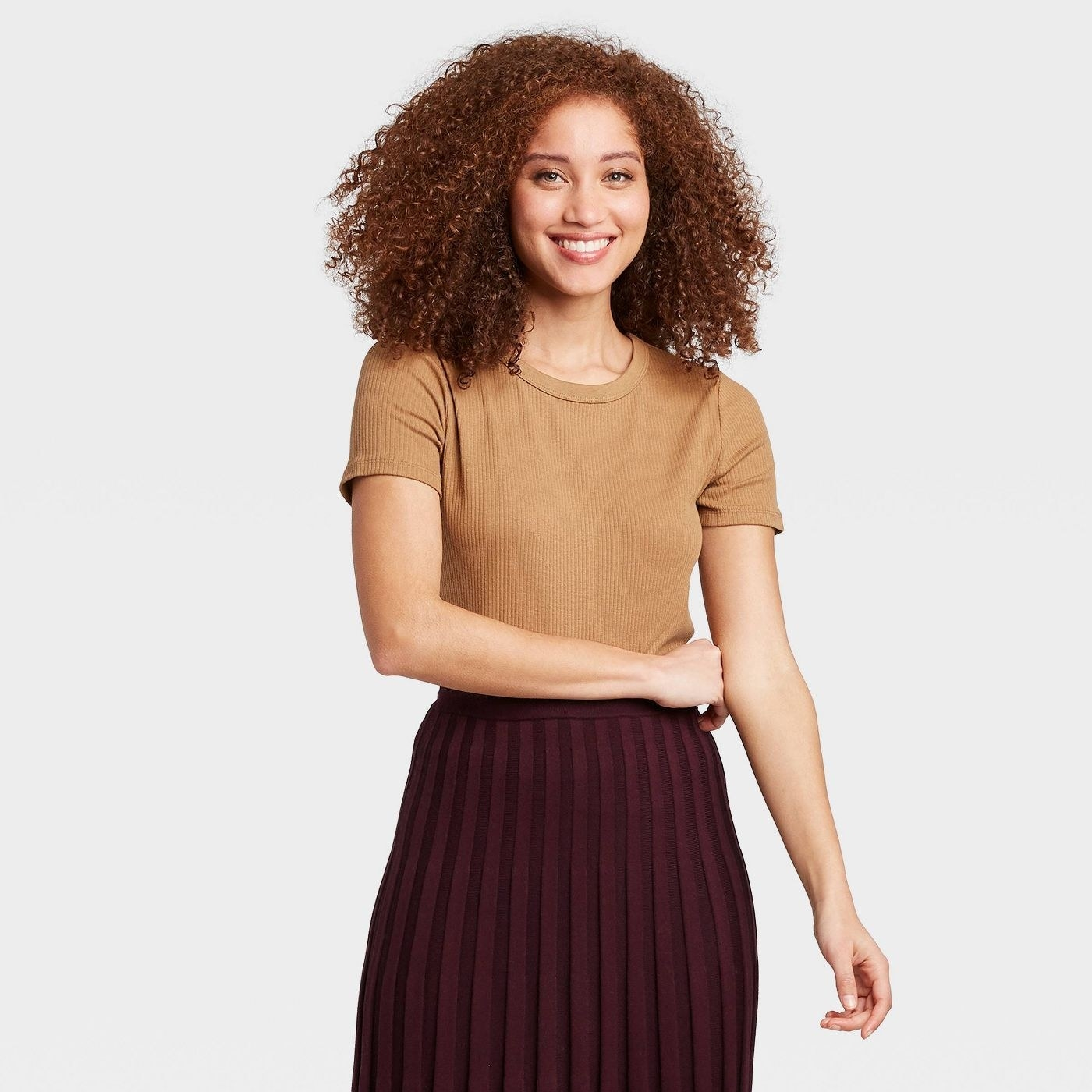 A smiling person wearing the t-shirt in brown and a brown skirt