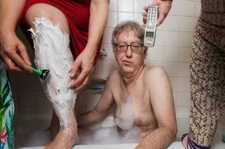 Man in bathtub with two women on either side of him