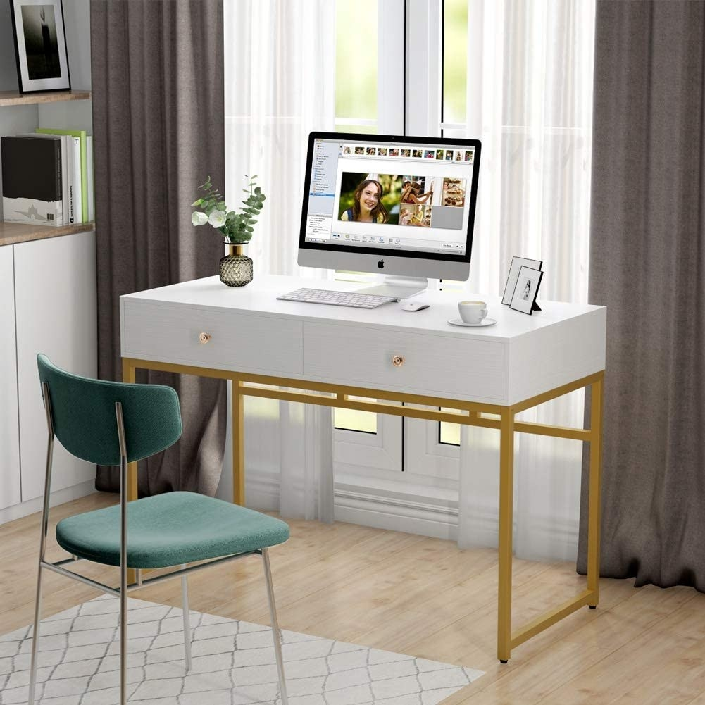 white desk with two front drawers and gold legs