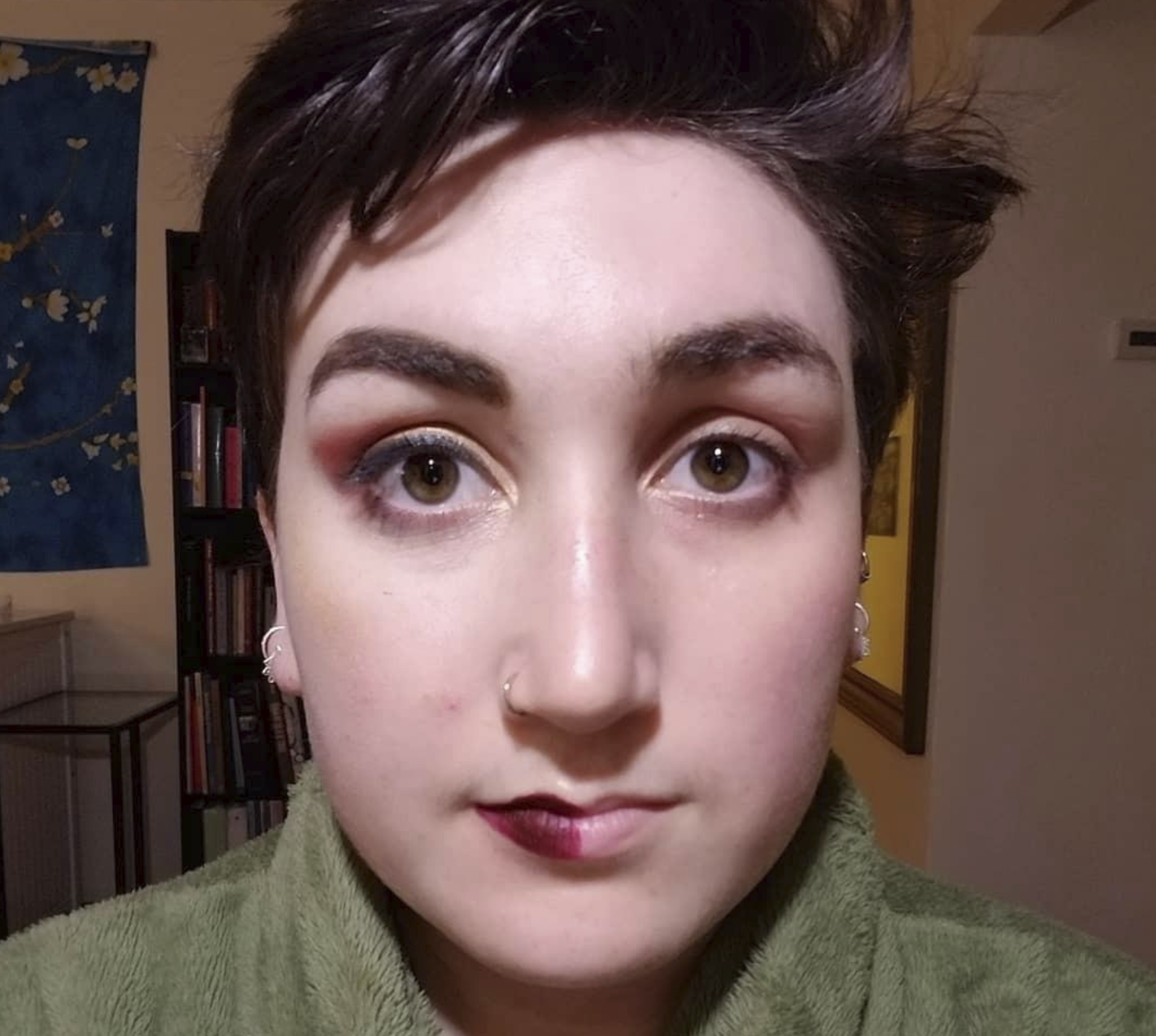 reviewer with half their face full of makeup and the other half with no makeup after it's been taken off by the cloths