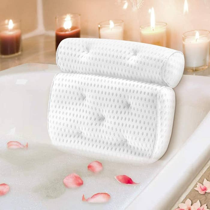 bath pillow on the bath tub surrounded by candles