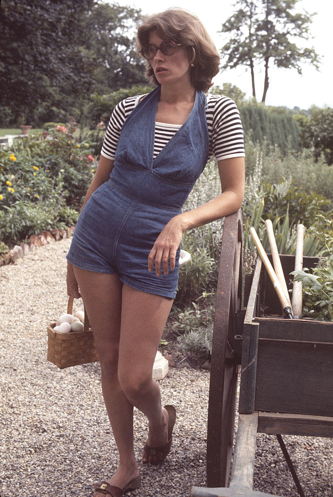 Martha Stewart carries a basket of eggs as she leans against a wheelbarrow on the grounds of her home, Westport, Connecticut, August 1976