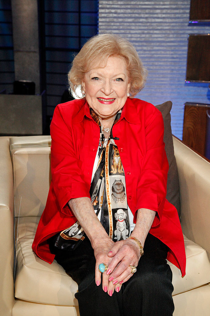 betty white with her hands folded on her lap smiling