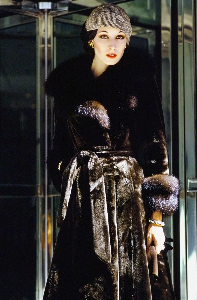 Anjelica Huston standing in front of a revolving door wearing sealskin wrap-and-tie fur coat with sable collar and cuffs by Emeric Partos