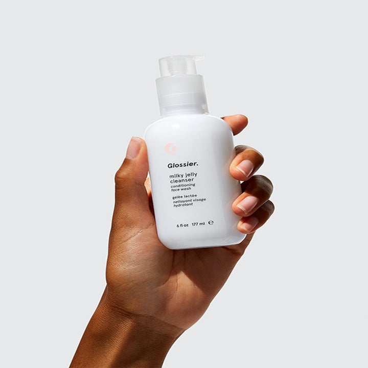 """Hand holds white bottle that says """"Glossier Milky Jelly Cleanser"""""""
