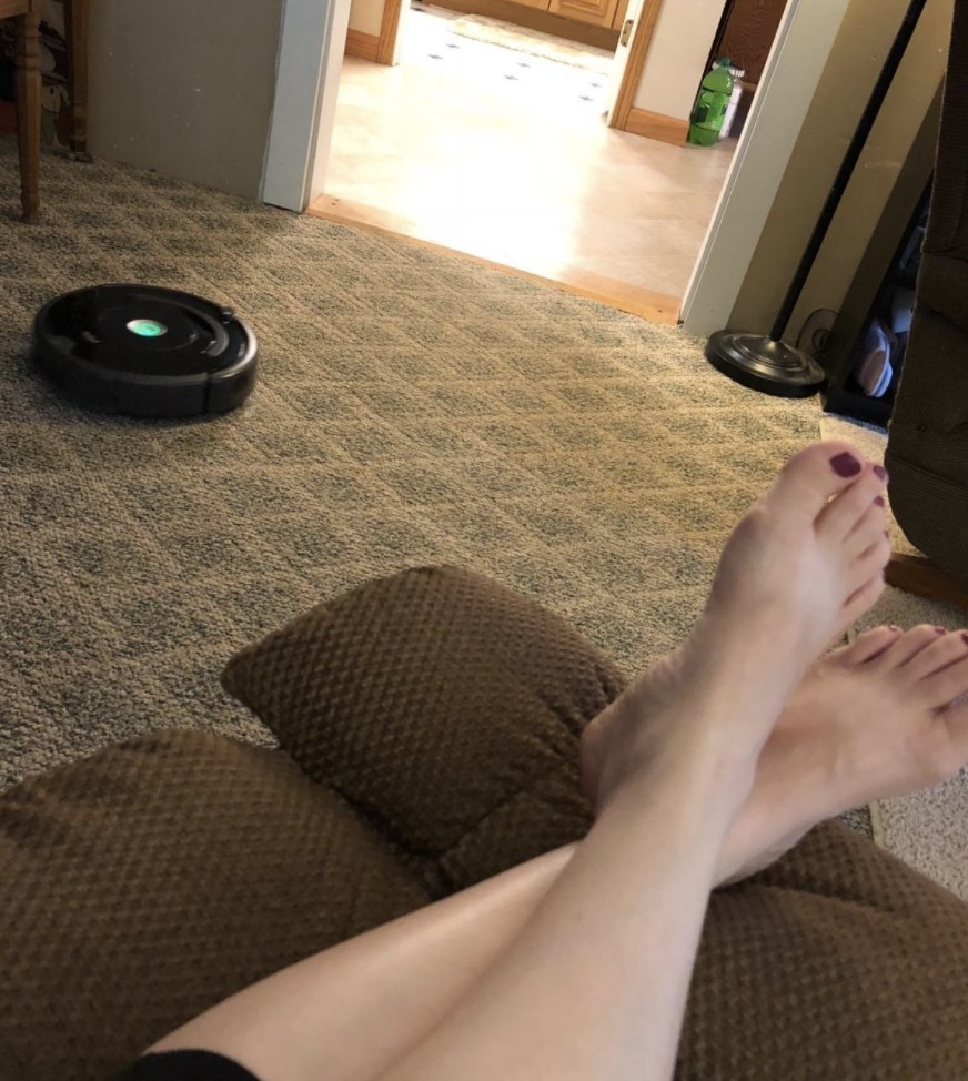 Person is sitting on the couch watching the Roomba vacuum work