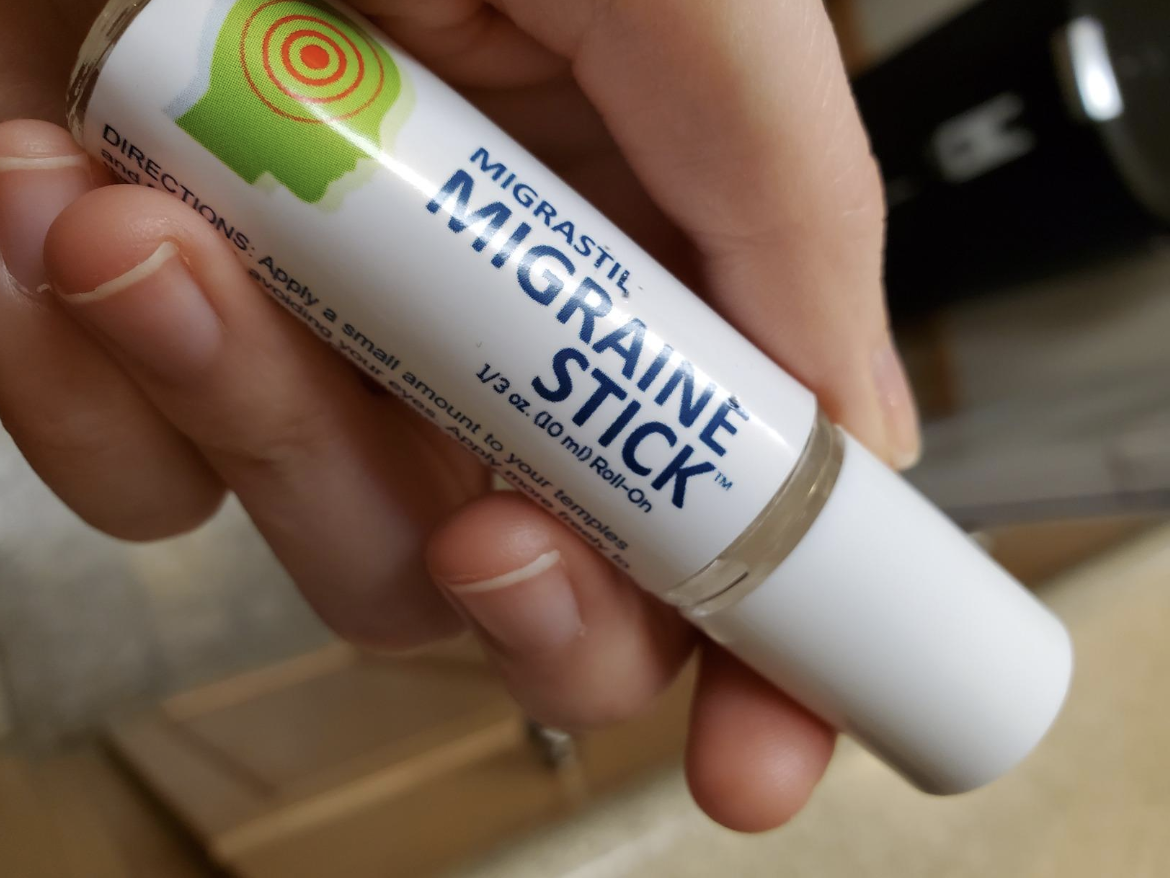 Reviewer holding lip balm-sized tube of roll on migraine stick