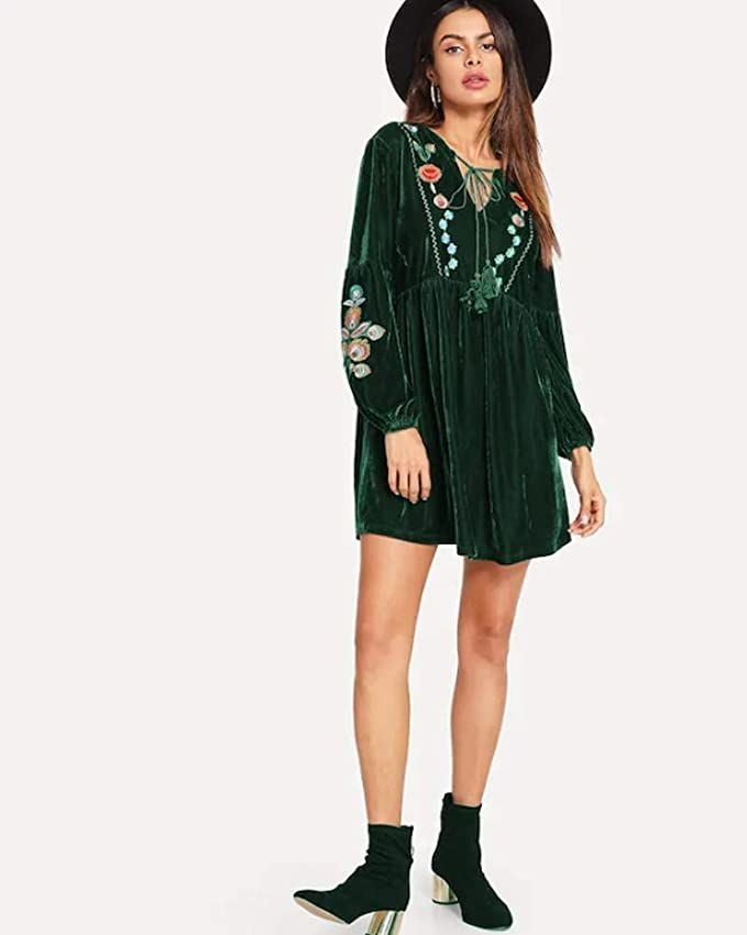 Model wearing the mid-thigh length dress in velvet green with embroidery on the sleeves and chest