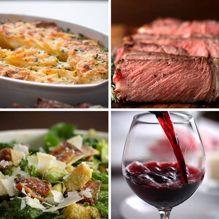 Salad, steak, potatoes, and red wine for two people