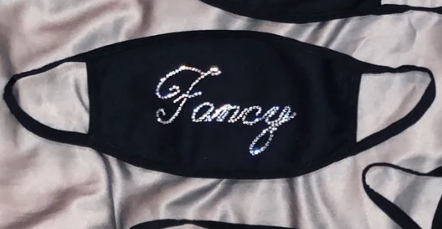 "A black face mask with bedazzled message that says ""fancy"""