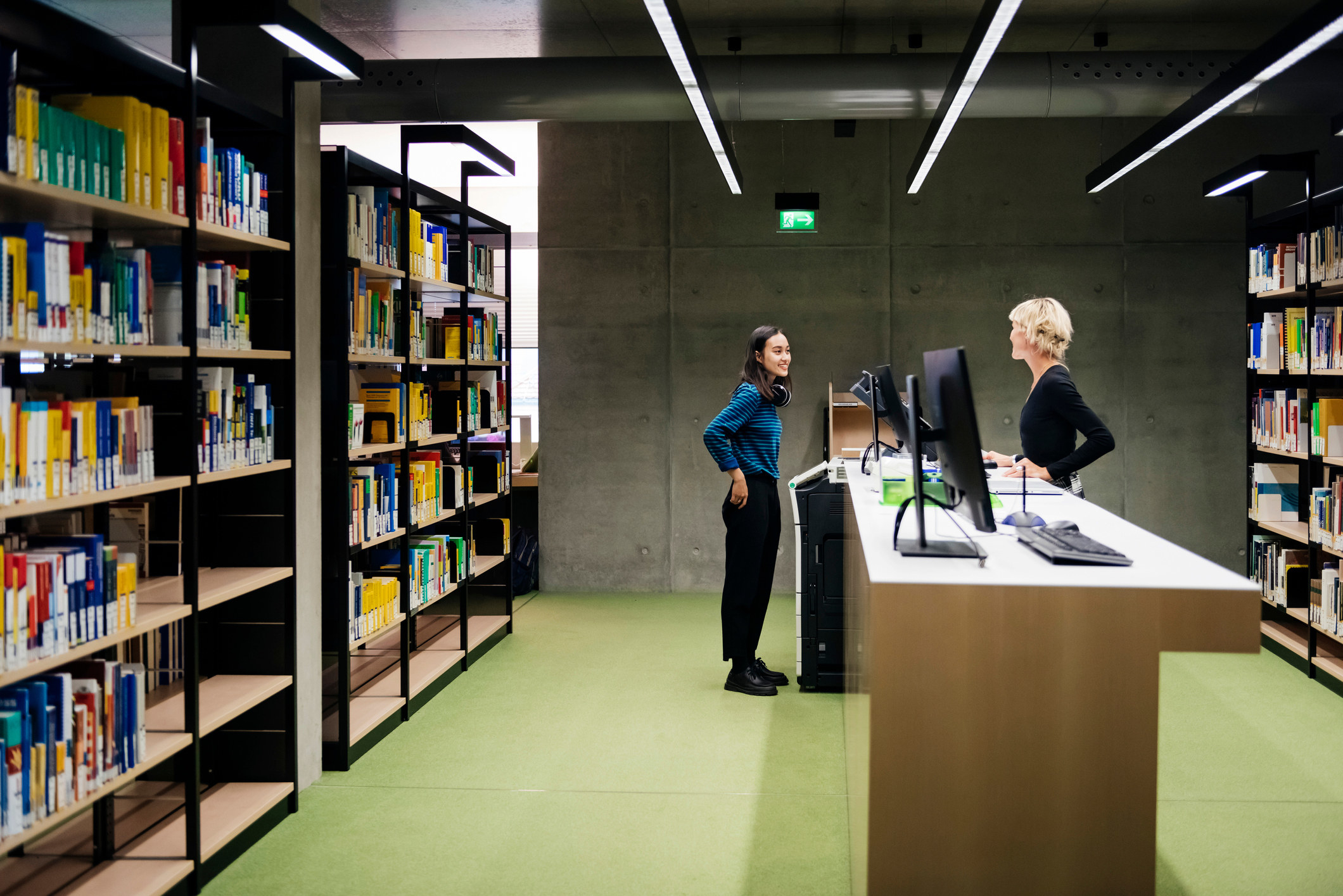 A student talking to a librarian, asking for help in a large, modern library.