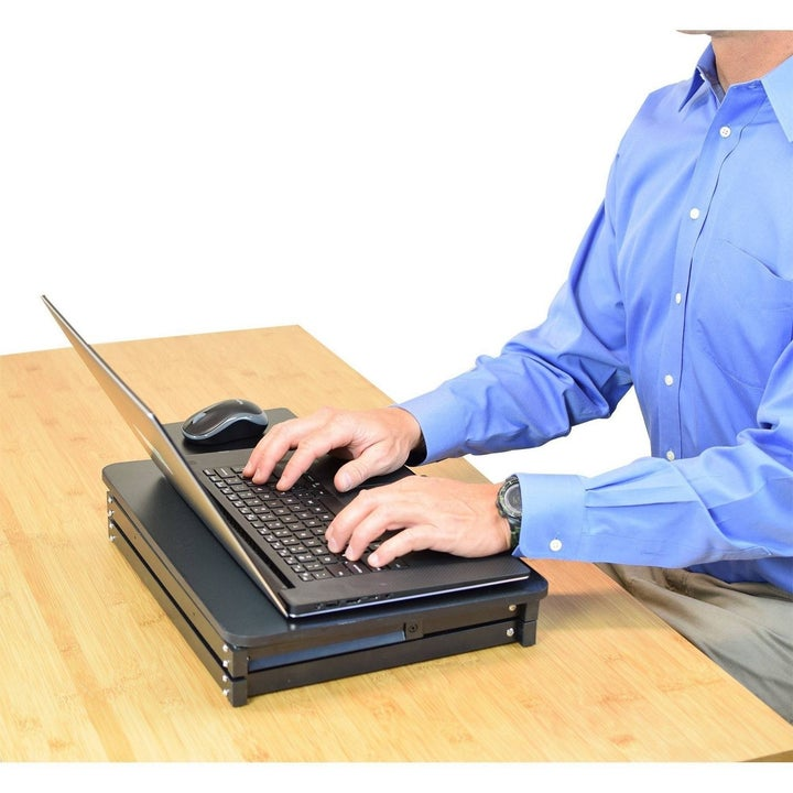 model using laptop on collapsed stand on a desk