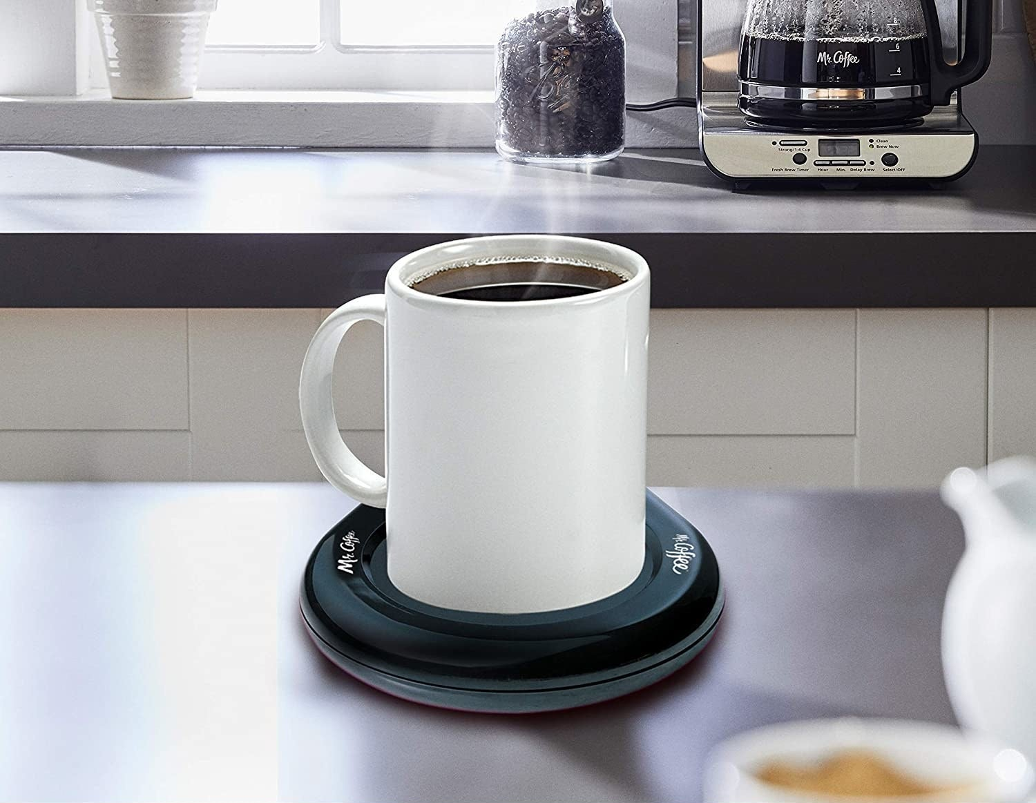 A mug on a black round mug warming surface on a table