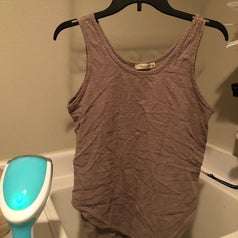 A reviewer photo of a tank top on a winkled hanger