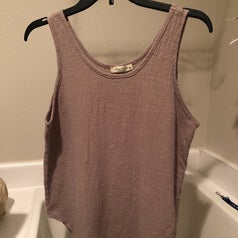 A reviewer of the same tank top on a hanger devoid of wrinkles