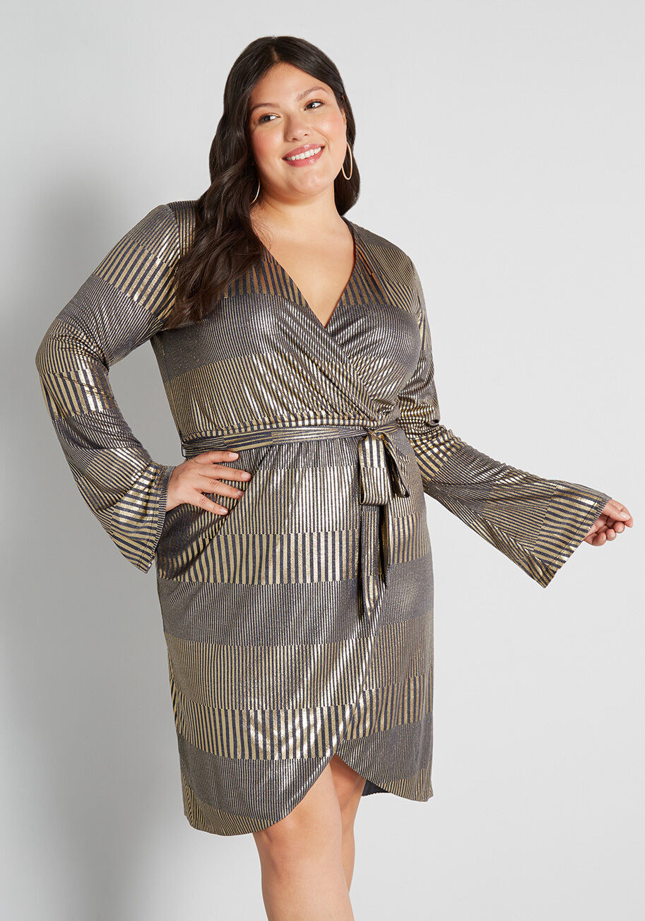 Model wearing the wrap dress with wide sleeves and a gold and silver striped pattern