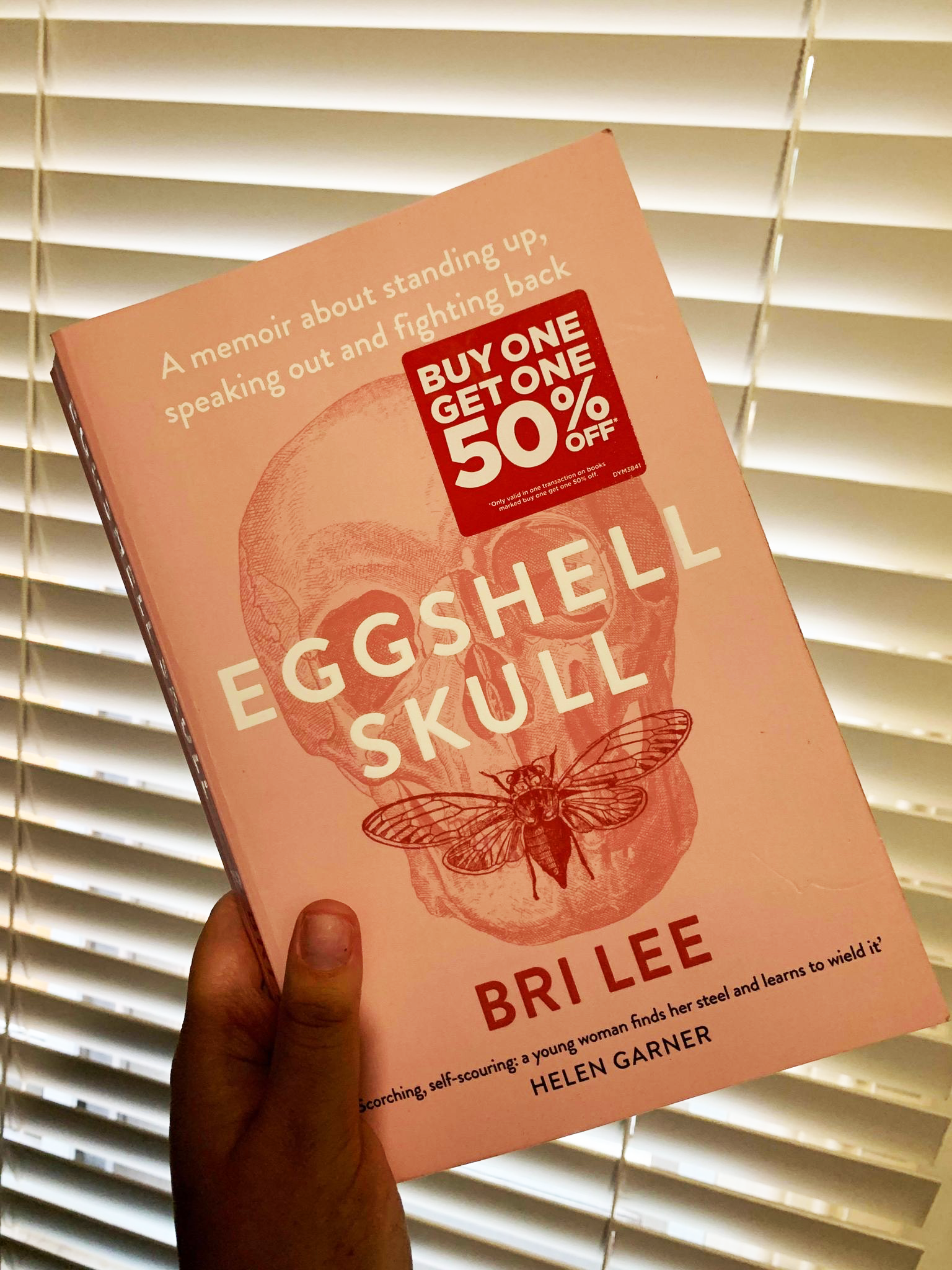 Book cover shows a faint etching of a skull with a winged insect stretching across the mouth
