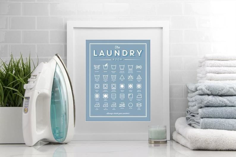 """A framed blue sign with white text that says """"The Laundry Room"""" and shoes wors of various laundry care symbols"""