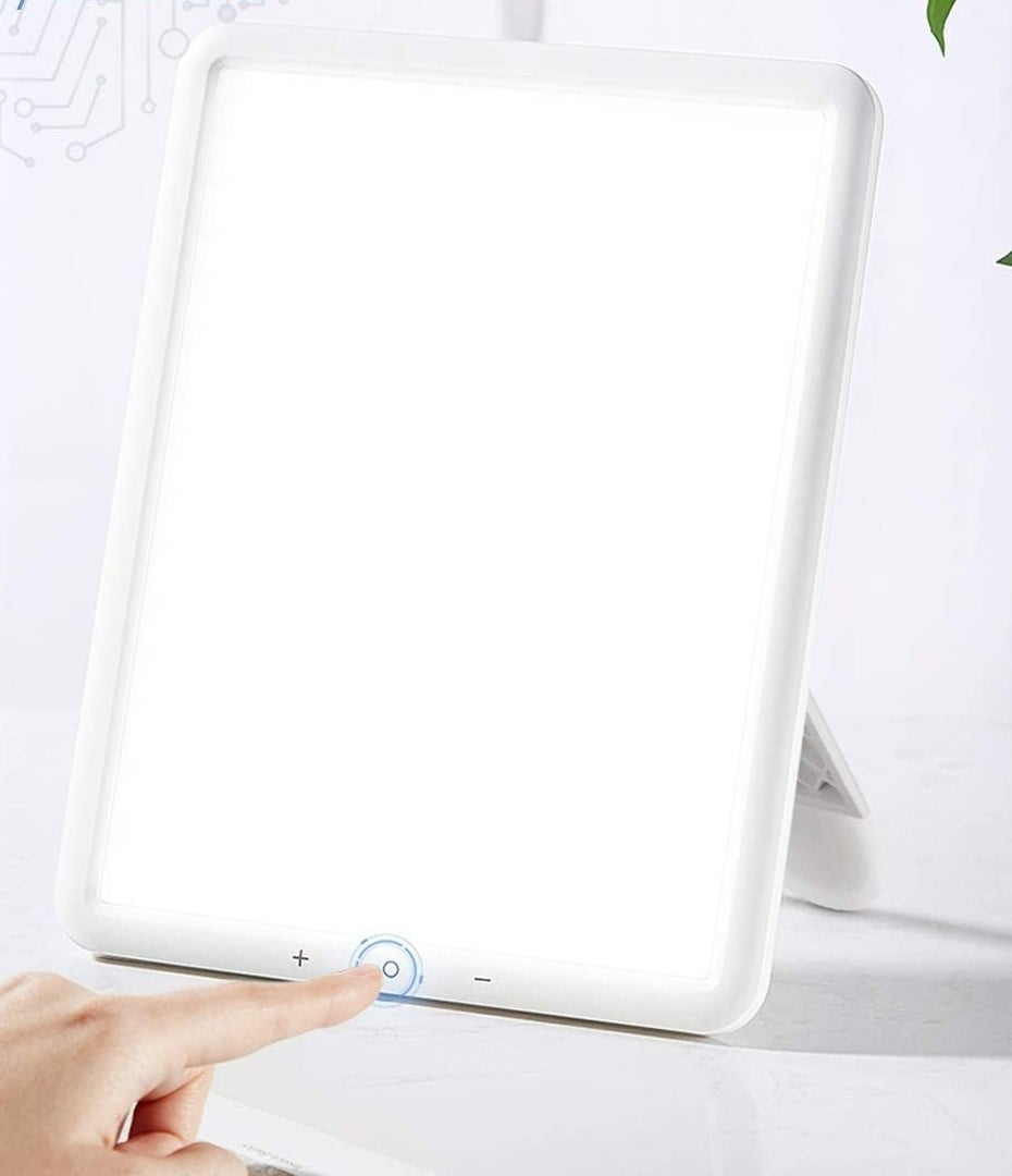 person pressing the power button on the light therapy lamp