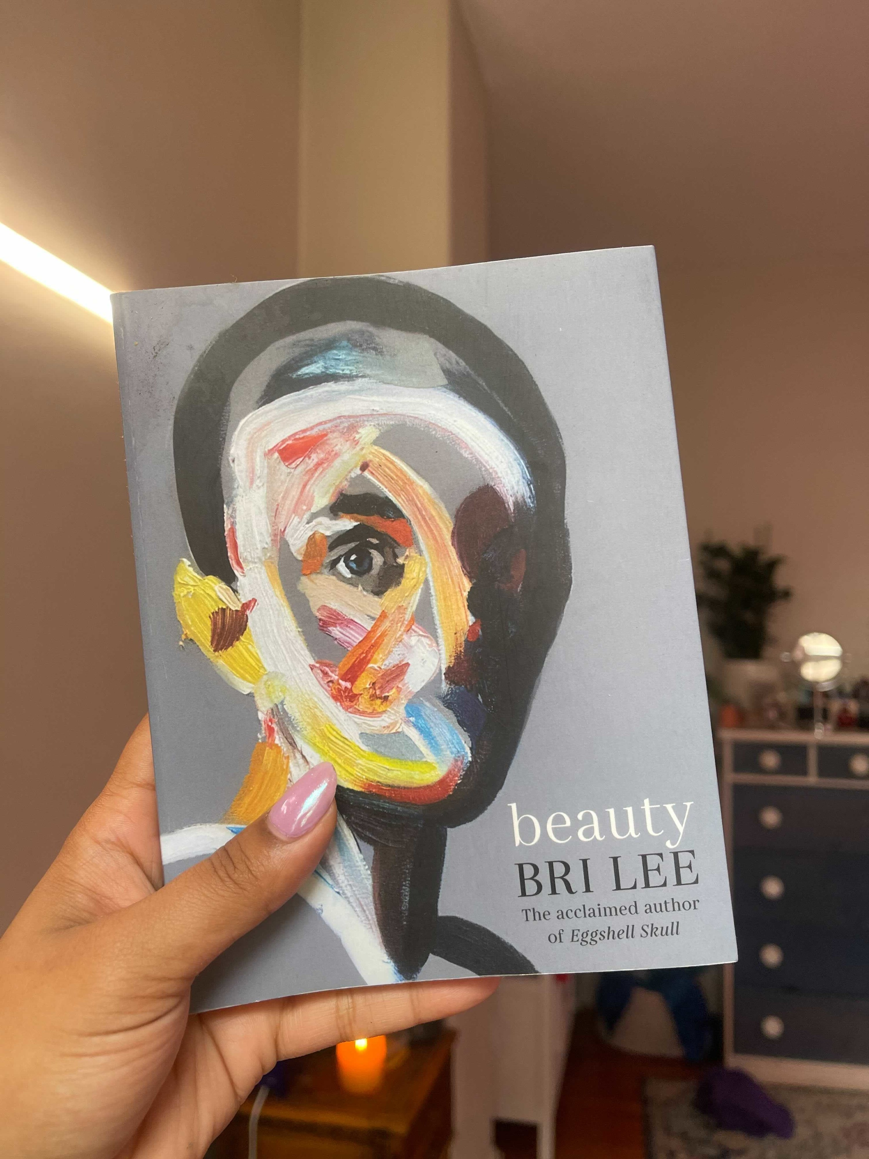 Person holding a small book that shows an abstract face painted with wide brush strokes and a piercing eye