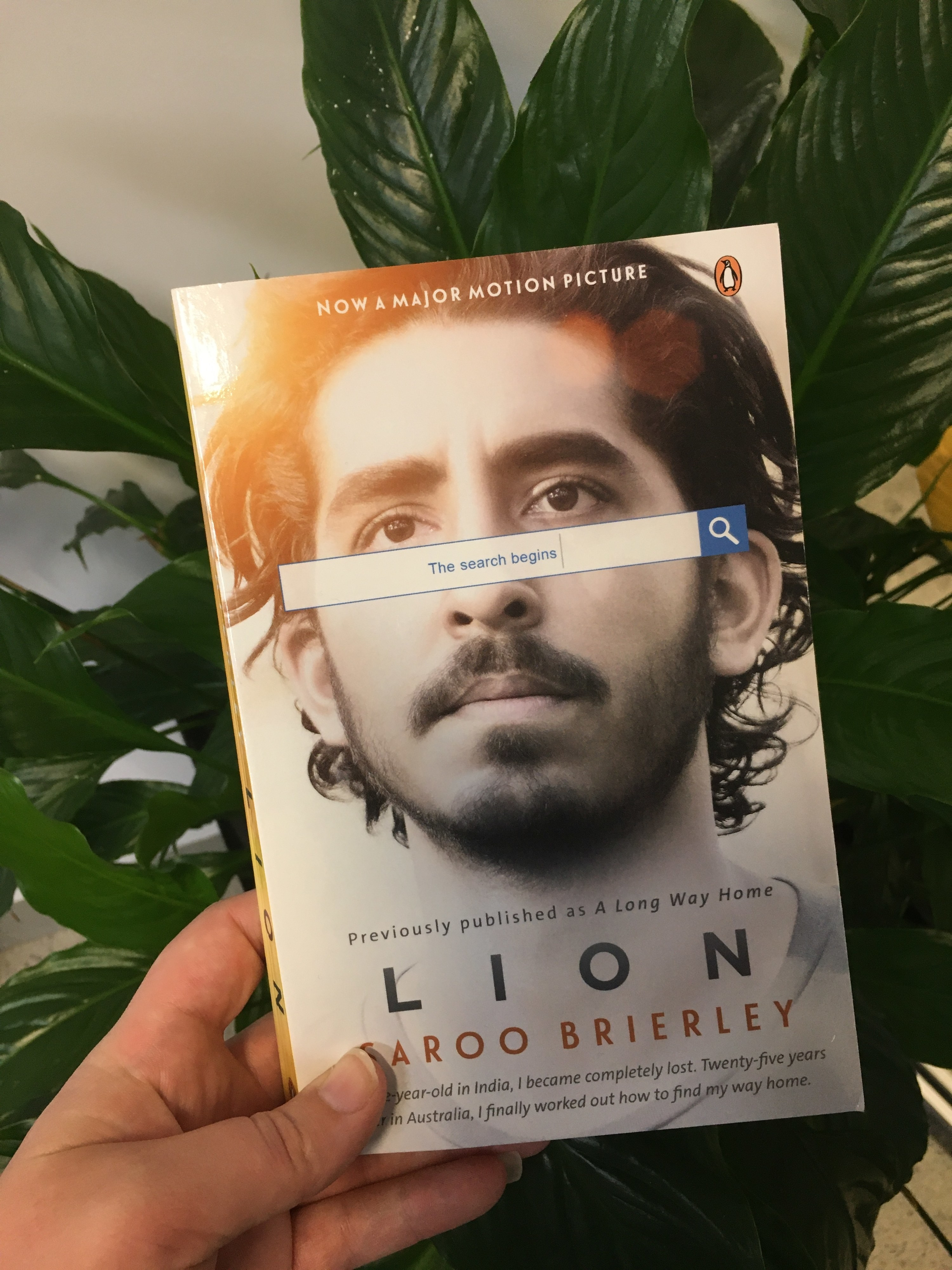 Hand holding book in front of a plant, cover of book is a face with a Google search bar in front of it