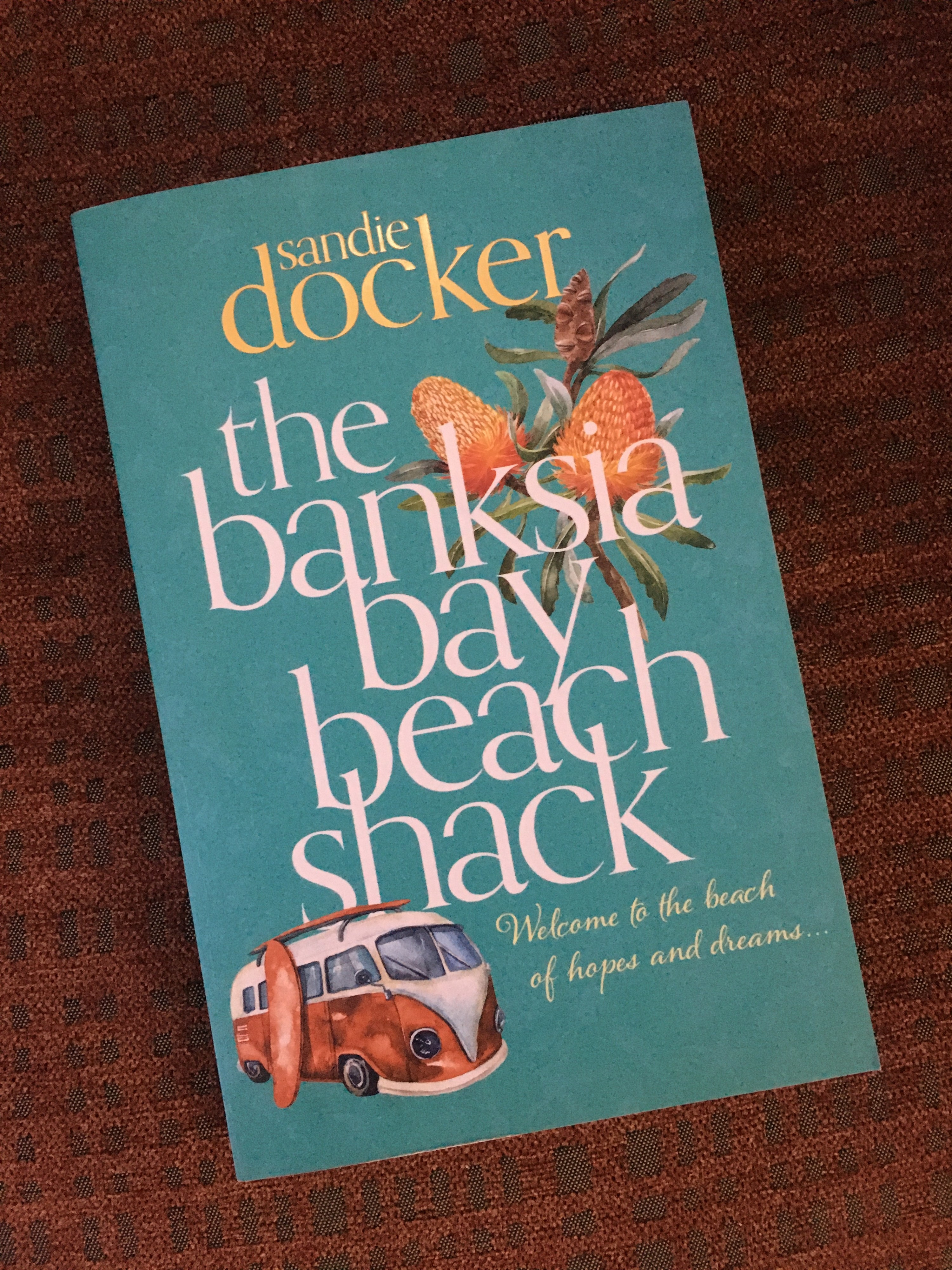 A book with a light cover, a picture of a banksia and old-school van