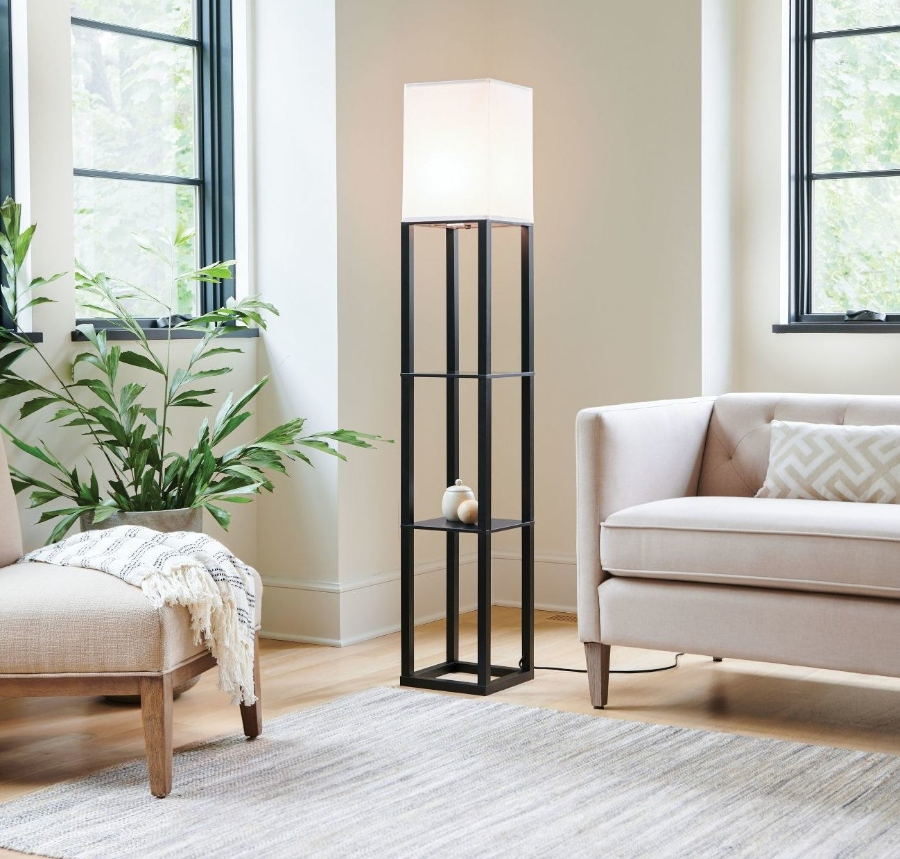 A black shelved floor lamp stand with a white shade