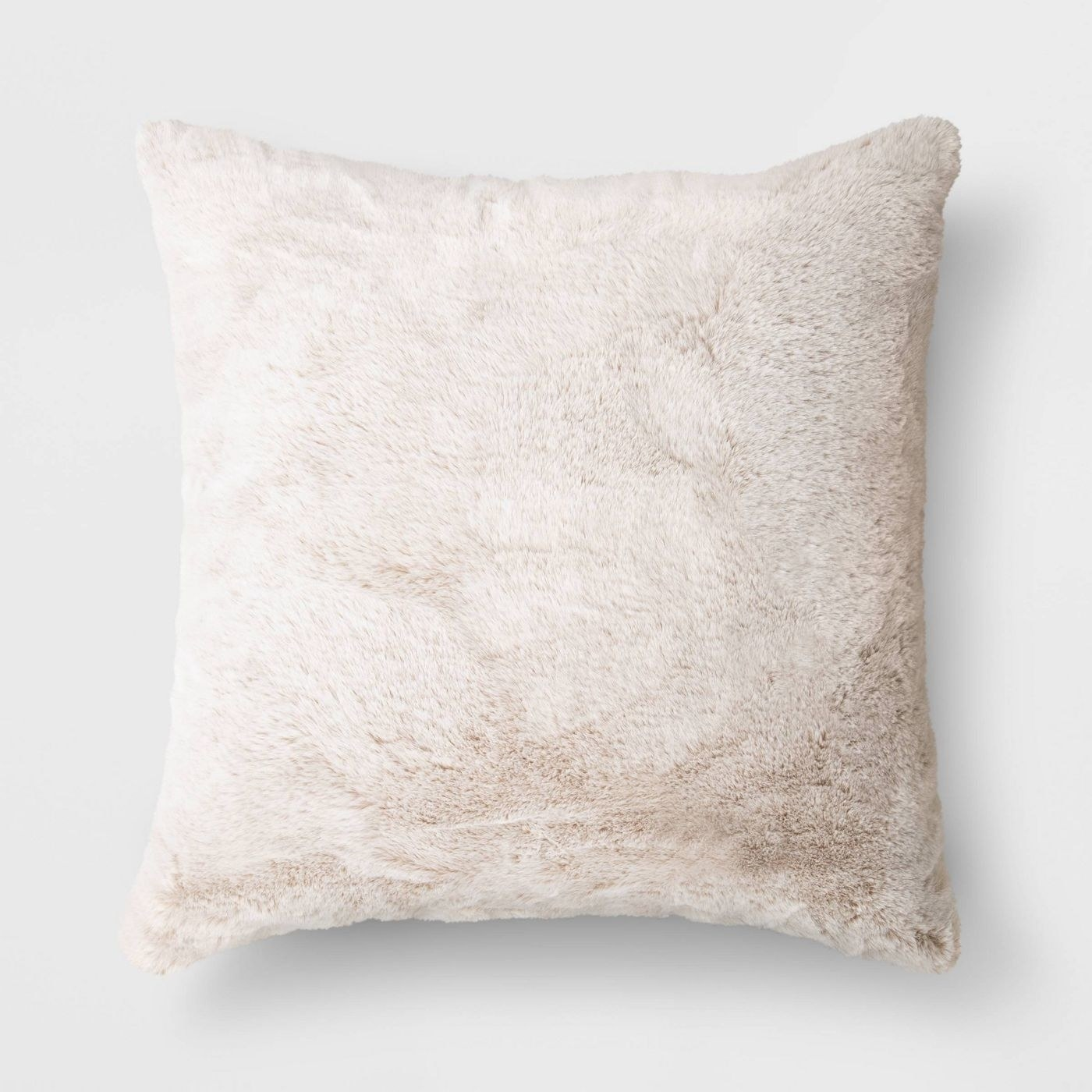 A neutral faux fur throw pillow