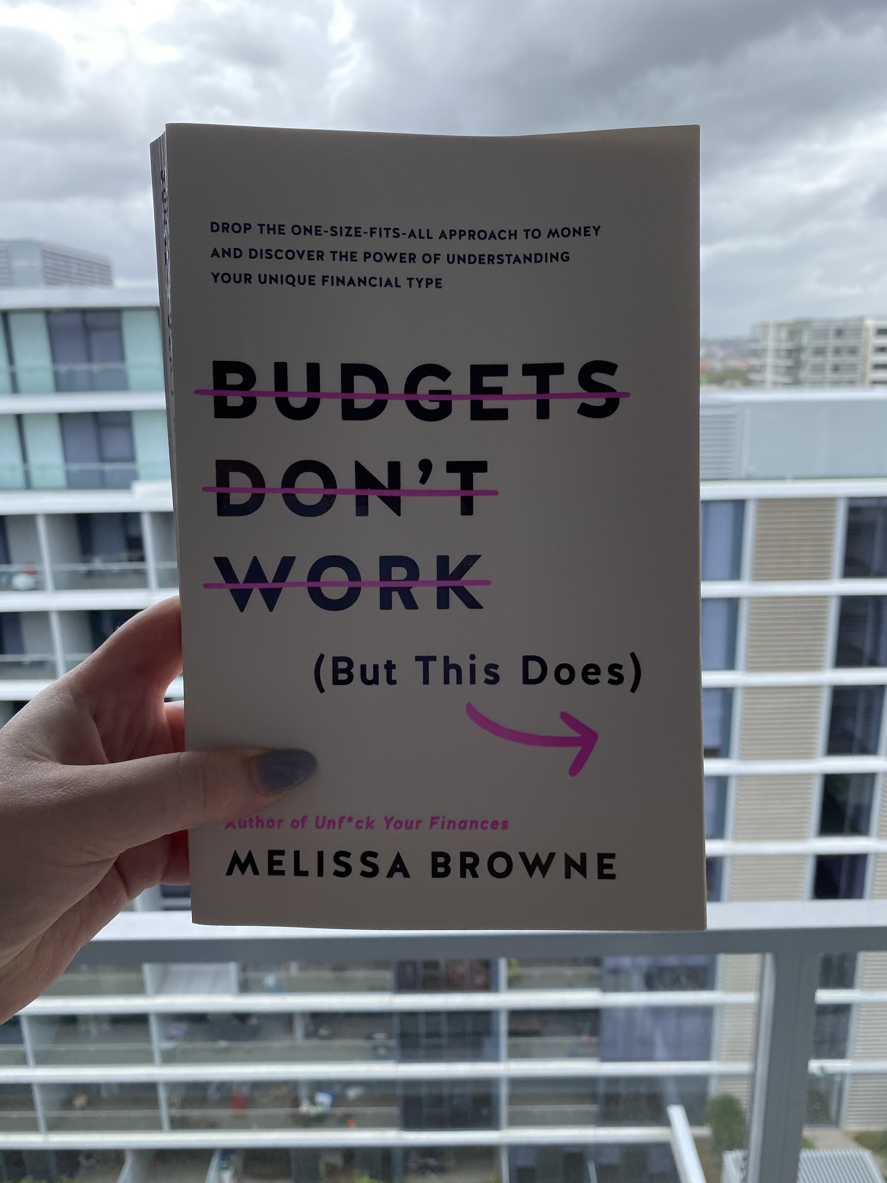 """Hand holding a book over a balcony with half the title, """"Budgets Don't Work"""" with a line through them"""