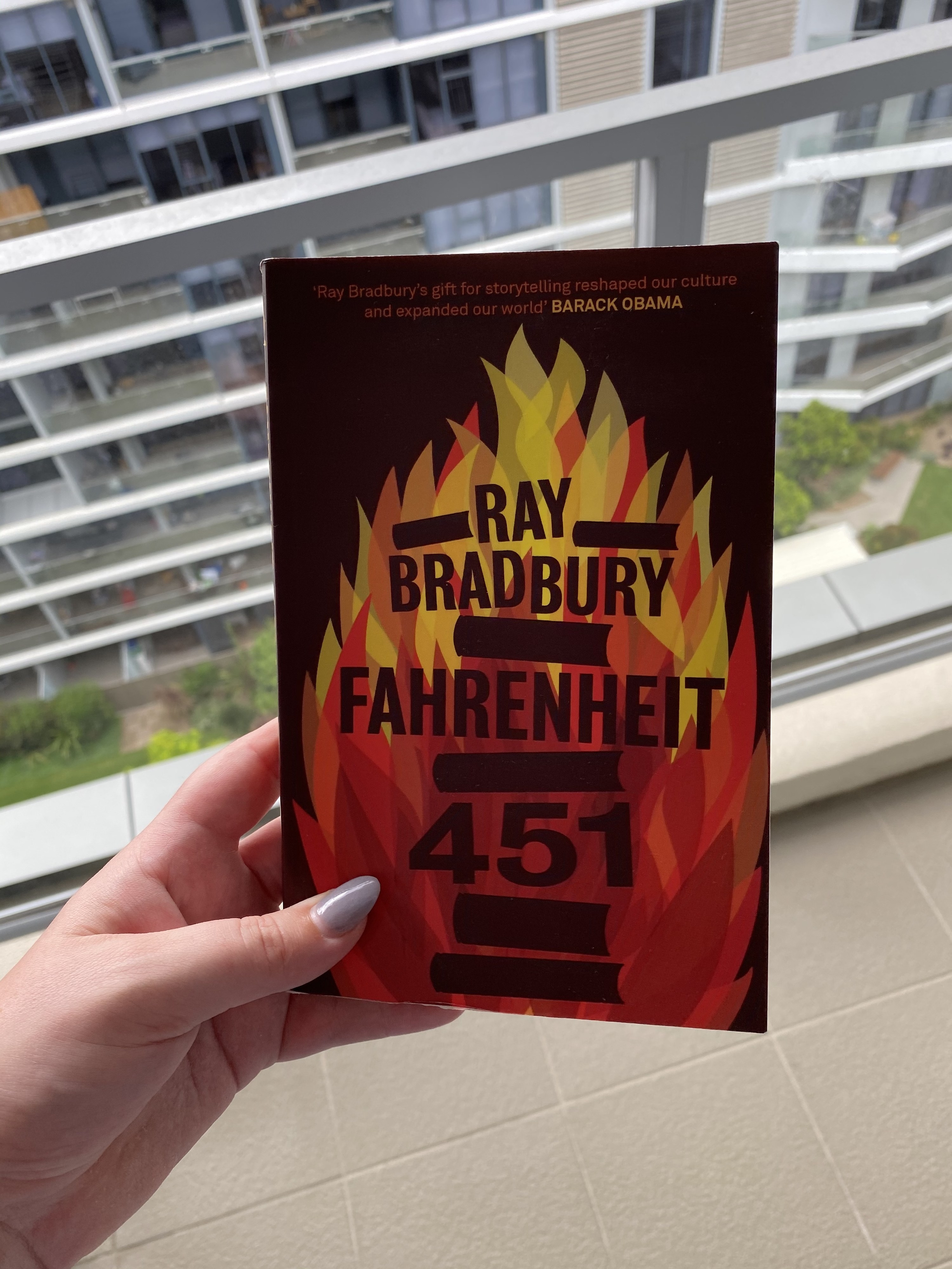 Hand holding book over balcony; cover shows flames with book silhouettes