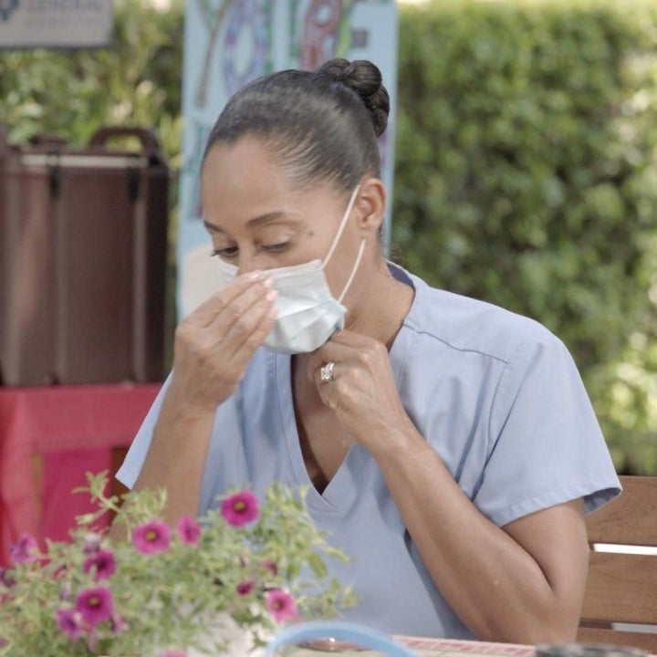 "A character from ""Black-ish"" sits at a table; she is wearing scrubs and a mask on her face"