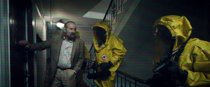 A shot from the film shows a plainclothes man with people in hazmat suits in a hallway