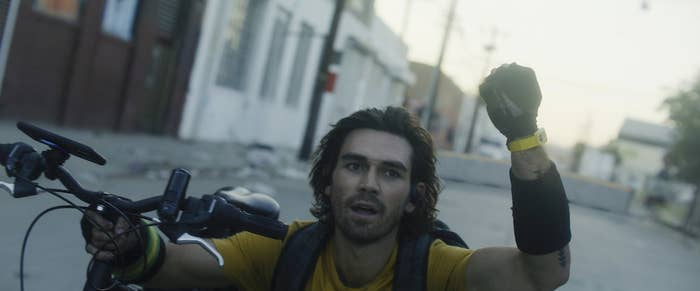A shot from the film shows KJ Apa holding up a fist while holding onto a bicycle