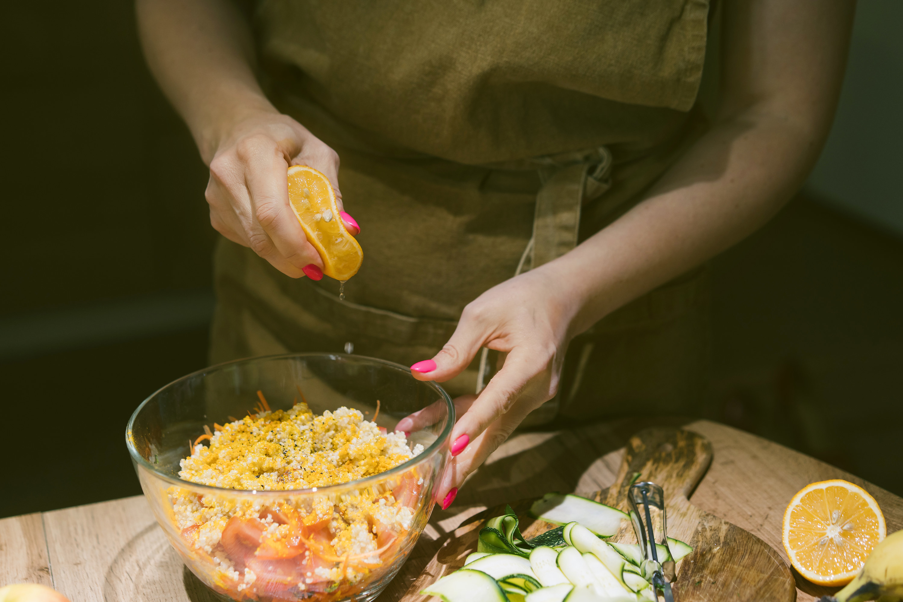 Hands squeezing lemon juice on a vegetarian salad of quinoa, tomato, carrot and spices