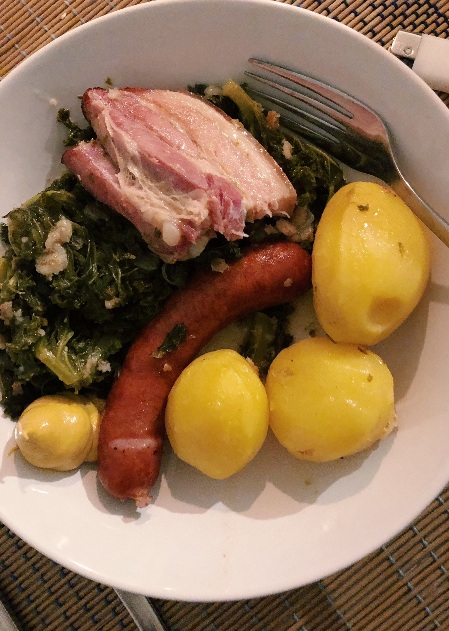 Homemade German kale stew with smoked sausage and boiled potatoes