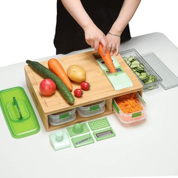 person grating a carrot with the grater that drops the shavings into the container below