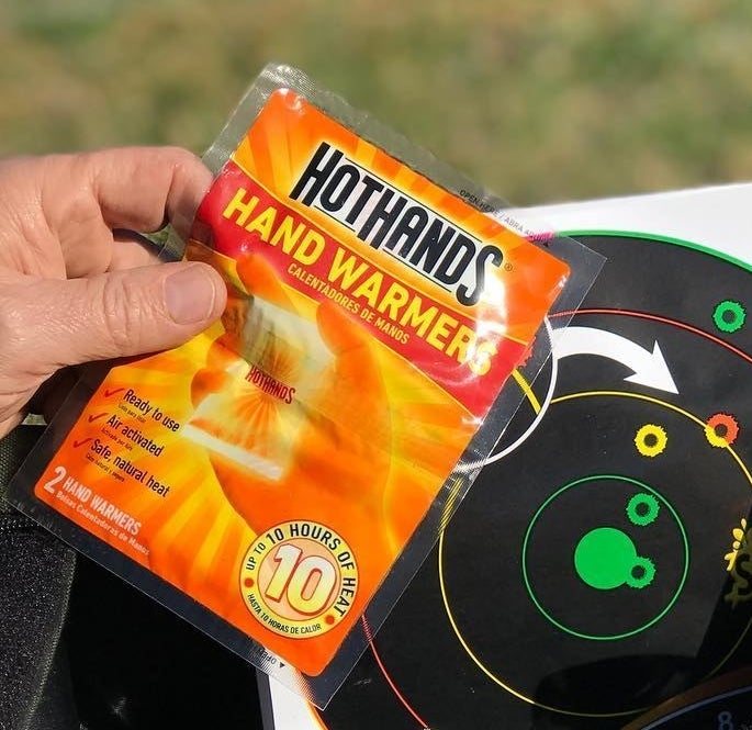 A person holding pack of handwarmers